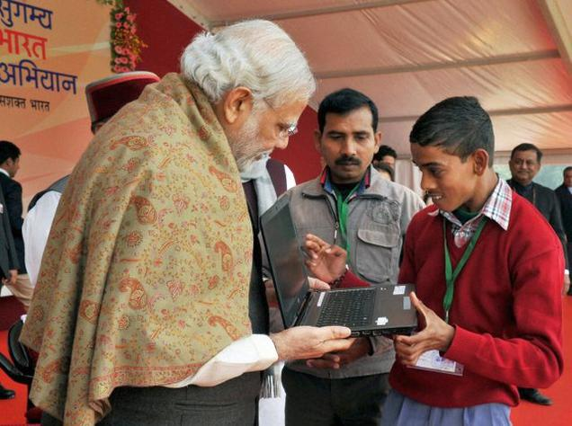 Prime Minister Narendra Modi interacts with a physically challenged child while distributing assistive devices at a function, in Varanasi on Friday.