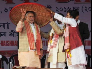 Prime Minister Narendra Modi being presented Jaapi, a traditional hat from Assam at a meeting in Sivasagar district on Friday.
