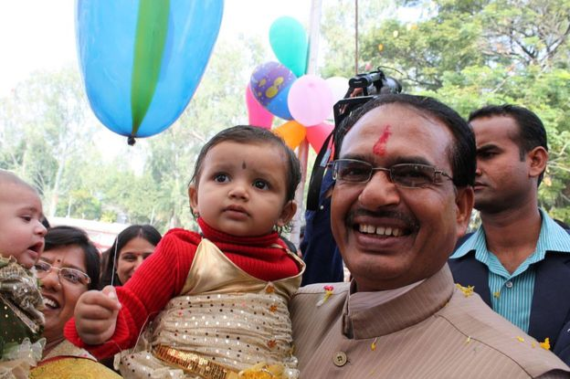 In this photograph taken on October 5, 2011, Chief Minister for the central Indian state of Madhya Pradesh Shivraj Singh Chouhan (R) poses with a child at a function to honour the 'girl child' in Bhopal